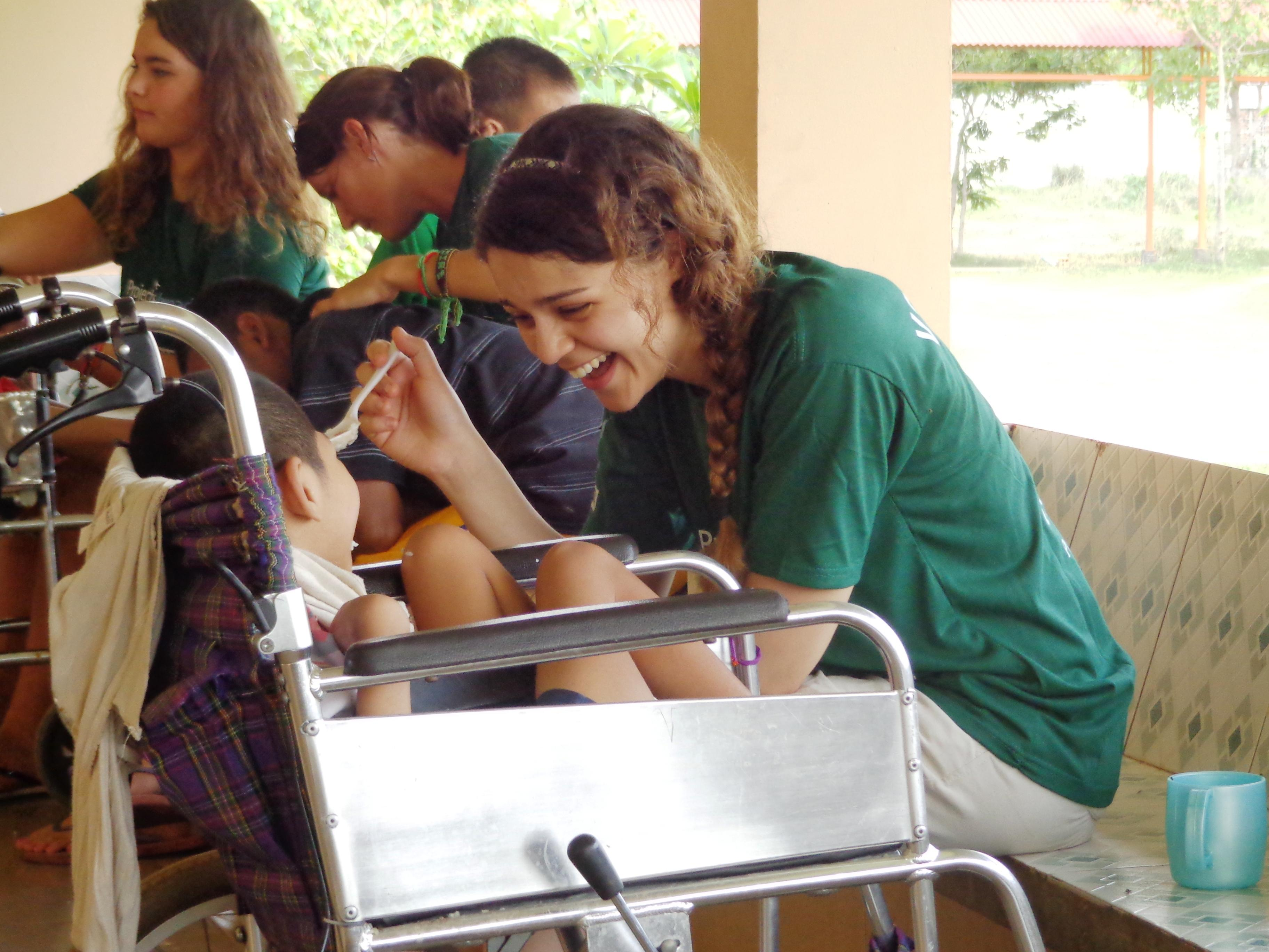 A female Projects Abroad intern is seen helping a child eat as part of her occupational therapy internship in Cambodia.